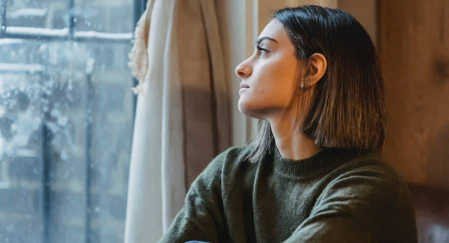 girl sitting by the window and looking sadly